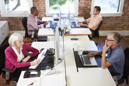 open plan: Group Of Workers At Desks In Modern Design Office Stock Photo