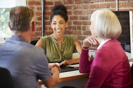 Senior paar ontmoeting met financieel adviseur In Office
