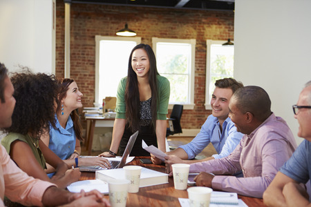 Female Boss Addressing Office Workers At Meeting Standard-Bild