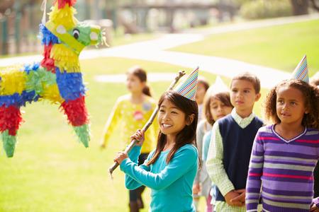 Kinderen raken Pinata Op Birthday Party Stockfoto