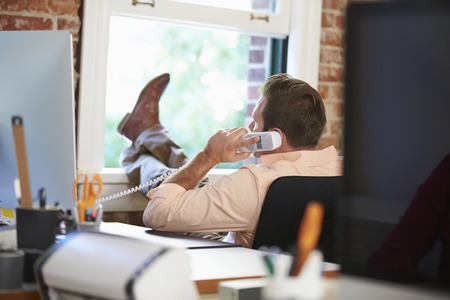 empleado de oficina: El hombre de negocios en el tel�fono que se relaja en la oficina moderna creativa Foto de archivo