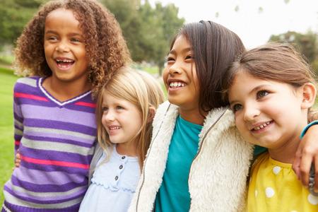 niños jugando en el parque: Grupo de chicas jóvenes que cuelgan hacia fuera en el parque Juntos