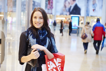 Female Shopper With Sale Bags In Shopping Mall 스톡 콘텐츠