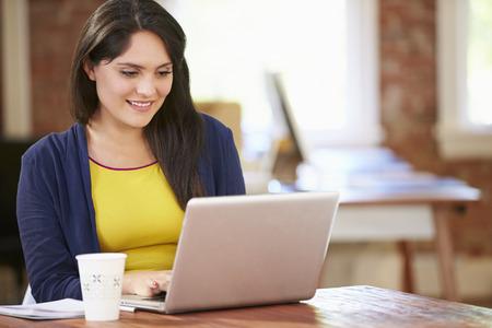 Vrouw die bij Laptop In hedendaagse kantoor