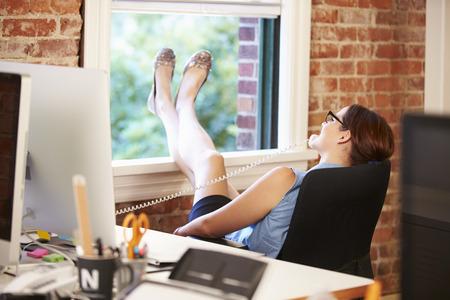 pies: Empresaria en el tel�fono que se relaja en la oficina creativa moderna