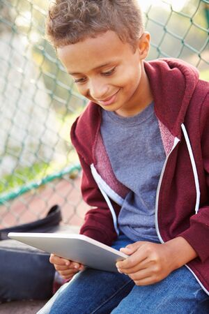 11 years: Young Boy Using Digital Tablet Sitting In Park
