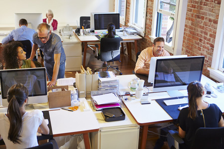open plan office: Wide Angle View Of Busy Design Office With Workers At Desks