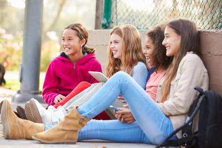 11: Young Girls Using Digital Tablets And Mobile Phones In Park Stock Photo