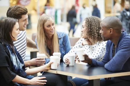 hombre tomando cafe: Grupo de amigos Reunión En Centro Comercial Caf