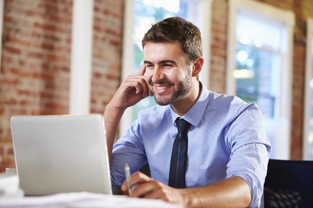 businessman laptop: Man Working At Laptop In Contemporary Office Stock Photo