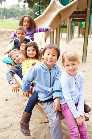 kinder spielen: Gruppe junge Kinder sitzen auf Plättchen im Spielplatz