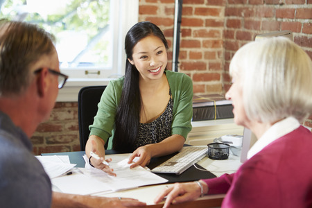 financial advisor: Senior Couple Meeting With Financial Advisor In Office