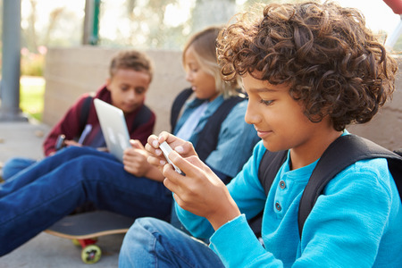 niños jugando: Young Boys Utilizando tabletas digitales y teléfonos móviles en el parque Foto de archivo