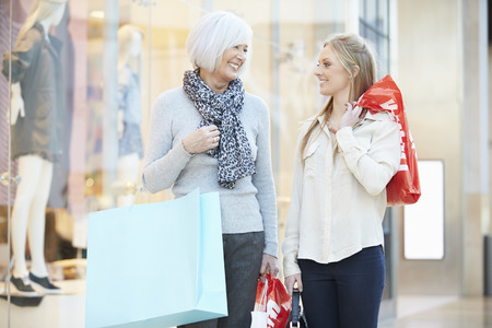shopping mall interior: Mother And Adult Daughter In Shopping Mall Together