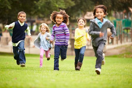 niños en area de juegos: Grupo de niños jovenes corriendo hacia la cámara en el parque Foto de archivo
