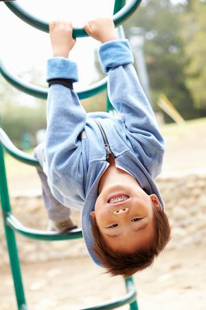 遊び場でフレームを登山上の少年 写真素材
