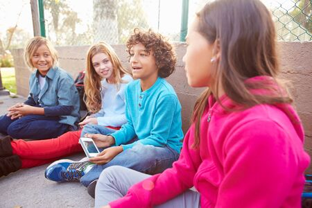 11 years: Group Of Young Children Hanging Out In Playground
