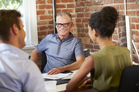 office meeting: Couple Meeting With Financial Advisor In Office Stock Photo
