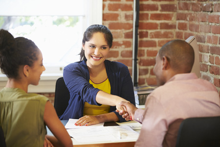 african american handshake: Couple Meeting With Financial Advisor In Office Stock Photo