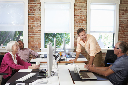 design office: Group Of Workers At Desks In Modern Design Office Stock Photo