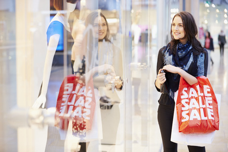 sales person: Female Shopper With Sale Bags In Shopping Mall Stock Photo