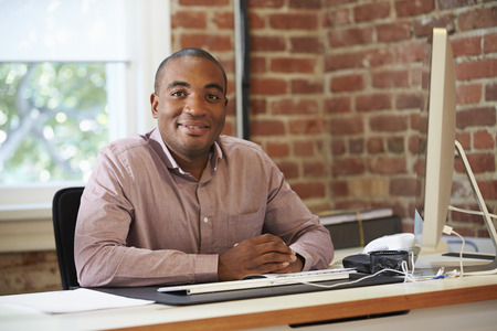 black men: Man Working At Computer In Contemporary Office