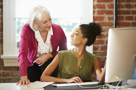 現代的なオフィス内のコンピューターで働く 2 人の女性