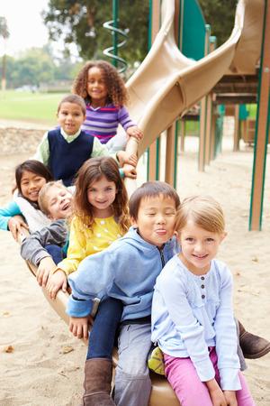 Groep Jonge kinderen zitten op de dia in Speelplaats
