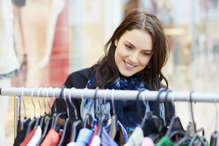 shopper: Woman Looking At Clothes On Rail In Shopping Mall Stock Photo