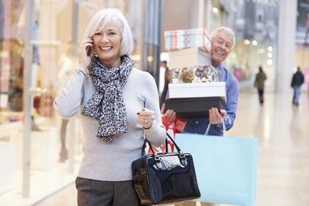 ancianos caminando: Mujer mayor de compras en el centro comercial como marido lleva Cajas