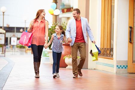 Familie, die durch Mall mit Einkaufstaschen