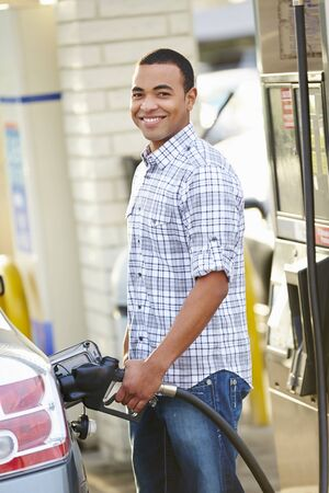 unleaded: Male Driver Filling Car At Gas Station Stock Photo