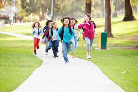 niños en area de juegos: Grupo de niños que ejecuta a lo largo Camino hacia la cámara en el Parque Foto de archivo