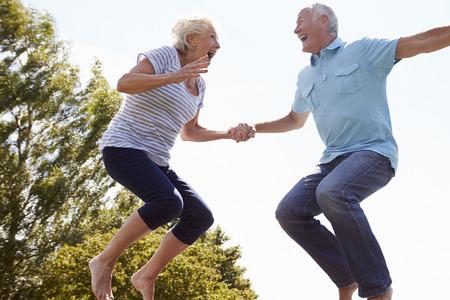 persona saltando: Pareja mayor rebotar en el trampolín en jardín