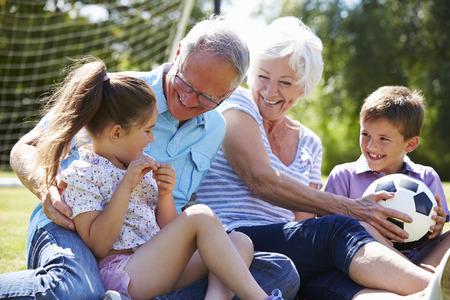 Grootouders en kleinkinderen voetballen in de tuin
