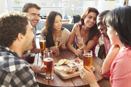 Groep vrienden genieten van drankje en een hapje In Rooftop Bar Stockfoto - 42308710