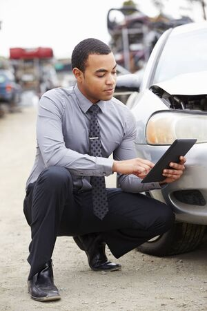 adjuster: Loss Adjuster Using Digital Tablet In Car Wreck Inspection Stock Photo