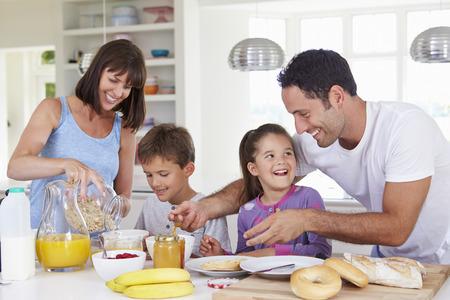 familia comiendo: Familia que hace el desayuno en cocina Juntos Foto de archivo