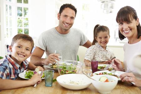 familias unidas: Familia que come la comida alrededor de la mesa de la cocina Juntos