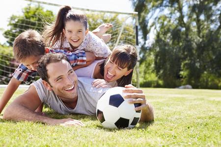 familias felices: Familia que juega al balompié en jardín junto Foto de archivo