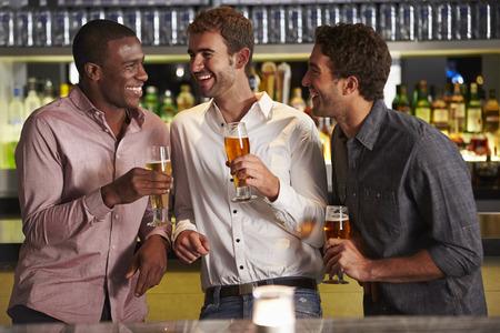 barra: Tres Amigos masculinos que disfrutan de la bebida en el bar Foto de archivo