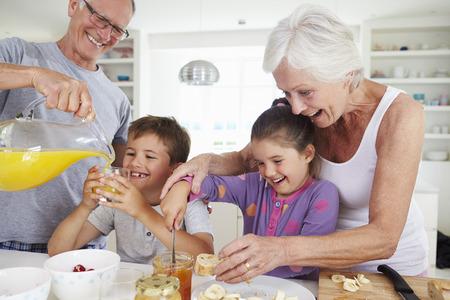 niños desayunando: Abuelos con los nietos Hacer el desayuno en cocina
