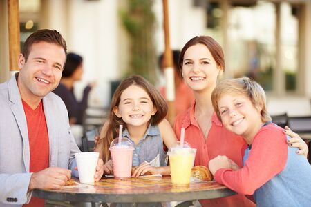 happy family shopping: Family Enjoying Snack In Caf� Stock Photo