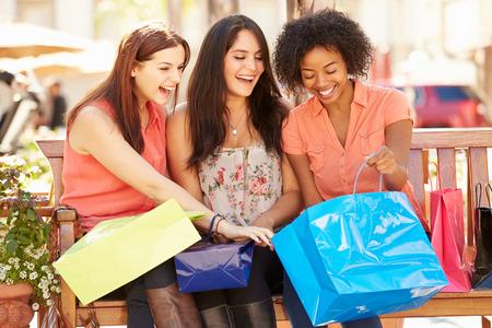 Tres amigos femeninos con los bolsos de compras que se sienta en el centro comercial Foto de archivo - 42308938