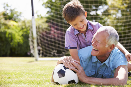 grandchild: Portrait Of Grandfather And Grandson With Football Stock Photo