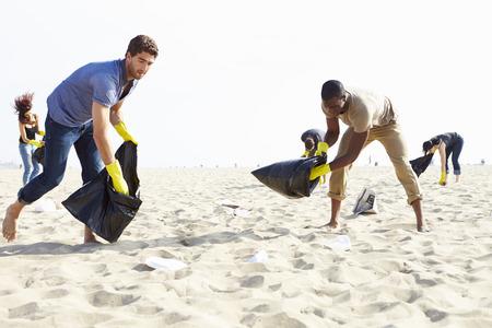 Groupe de bénévoles rangement détritus sur la plage Banque d'images - 42308937