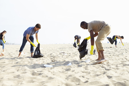 clean up: Group Of Volunteers Tidying Up Rubbish On Beach