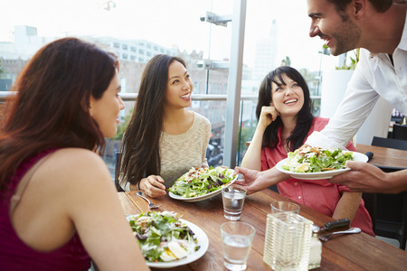 servings: Three Female Friends Enjoying Lunch At Rooftop Restaurant Stock Photo