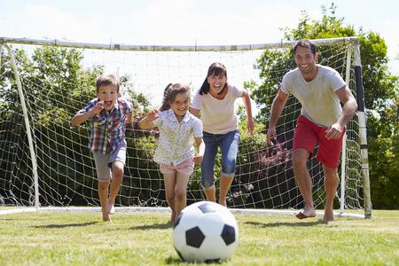 niño corriendo: Familia que juega al balompié en jardín junto Foto de archivo
