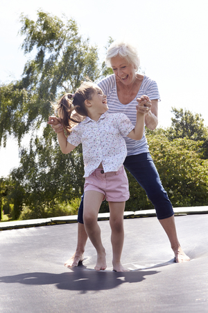 bouncing: Grandmother And Granddaughter Bouncing On Trampoline